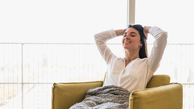 Retrato sonriente de una mujer joven con sus manos en la cabeza que se sienta en la butaca