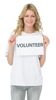 Retrato de una sonriente mujer joven voluntario celebración cartel