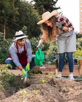 Retrato sonriente de una mujer que riega las plantas y un trabajador de sexo masculino que cava el suelo con la azada