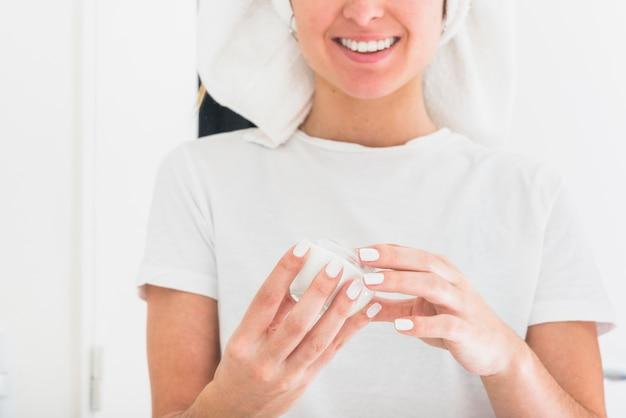 Retrato sonriente de la mujer que sostiene la botella poner crema de la crema hidratante en manos