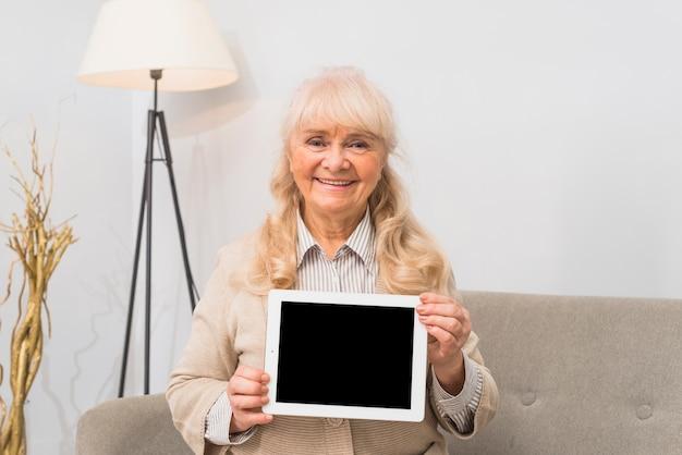 Retrato sonriente de una mujer senior mostrando tableta digital con pantalla en blanco