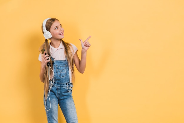 Retrato sonriente de una música que escucha de la muchacha en el auricular que señala en algo contra fondo amarillo