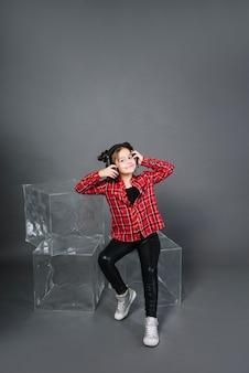 Retrato sonriente de una música que escucha de la muchacha en el auricular que se sienta en bloques transparentes contra fondo gris