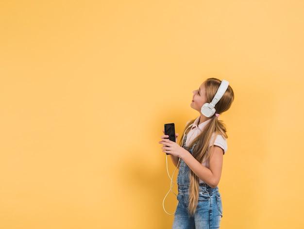Retrato sonriente de una música que escucha de la muchacha en el auricular que sostiene smartphone en la mano que mira el fondo amarillo