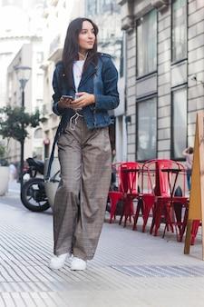 Retrato sonriente de una música que escucha de la mujer joven en el teléfono que se coloca en la calle