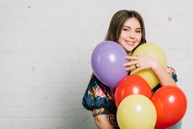 Retrato sonriente de una niña adolescente sosteniendo globos