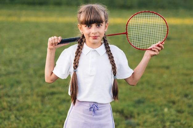 Retrato sonriente de una niña con bádminton