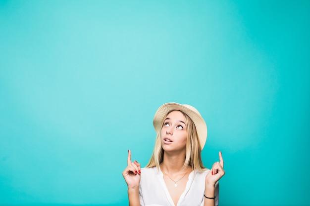 Retrato de una sonriente niña bonita de verano con sombrero de paja apuntando con dos dedos hacia arriba en copyspace aislado sobre la pared azul