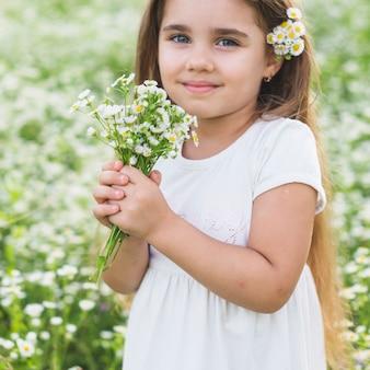 Retrato de sonriente niña hermosa con flores silvestres