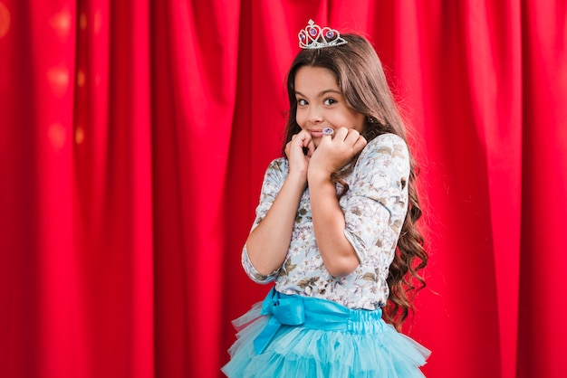 Retrato de sonriente niña linda tímida de pie delante de la cortina roja