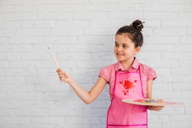 Retrato sonriente de una niña con pincel y paleta en la mano de pie contra la pared