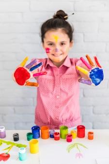 Retrato sonriente de una niña que muestra su mano pintada de colores