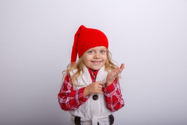 Retrato de sonriente niña rubia con sombrero de santa sobre fondos blancos