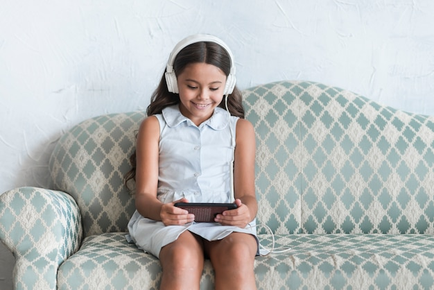 Retrato sonriente de una niña sentada en el sofá usando un teléfono móvil con auriculares en la cabeza