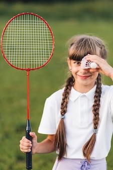 Retrato sonriente de una niña sosteniendo bádminton y volante sobre sus ojos