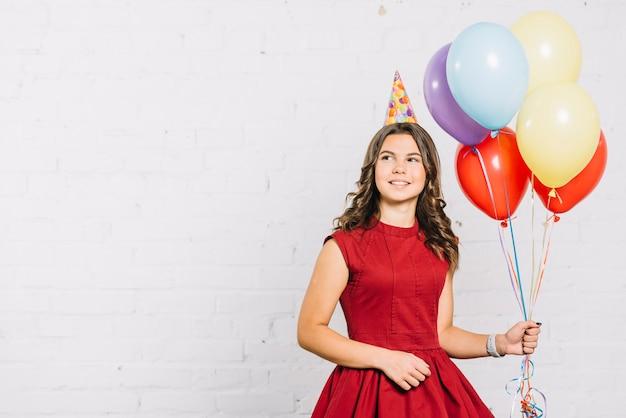 Retrato sonriente de una niña sosteniendo globos de colores en la mano