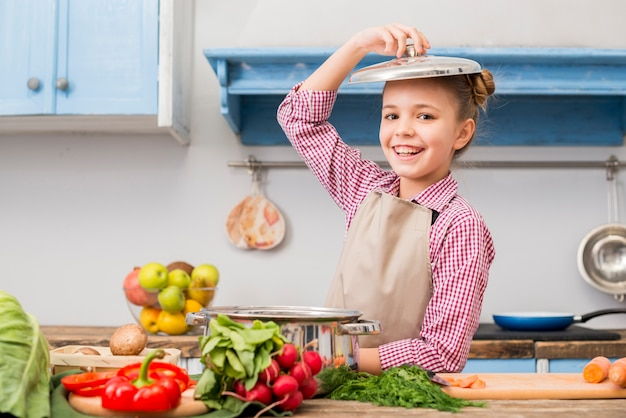 Retrato sonriente de una niña con tapa sobre su cabeza de pie en la cocina