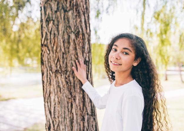 Retrato sonriente de una niña tocando el tronco de un árbol