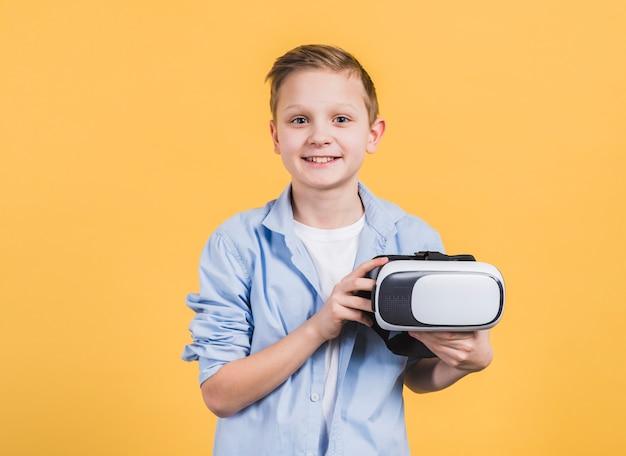 Retrato sonriente de un niño con gafas de realidad virtual en la mano contra el fondo amarillo