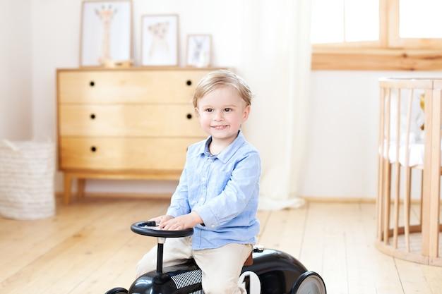 Retrato sonriente niño montando juguete vintage car. niño gracioso jugando en casa. vacaciones de verano y concepto de viaje. niño conduciendo un automóvil en la guardería. niño conduciendo un automóvil retro, niño en coche de juguete