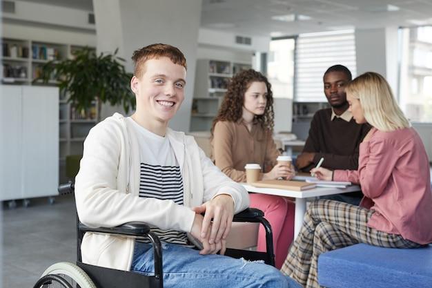 Retrato de sonriente niño pelirrojo con silla de ruedas estudiando con un grupo de estudiantes en la biblioteca de la universidad y,