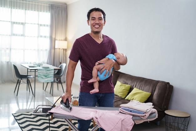 Retrato de sonriente padre asiático planchando su ropa mientras sostiene a su bebé en su mano