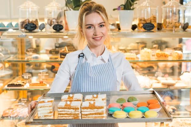 Retrato sonriente de un panadero femenino que sostiene la bandeja grande con los macarrones y los pasteles coloridos