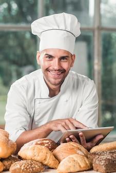 Retrato de sonriente panadero masculino usando tableta digital con muchos panes horneados