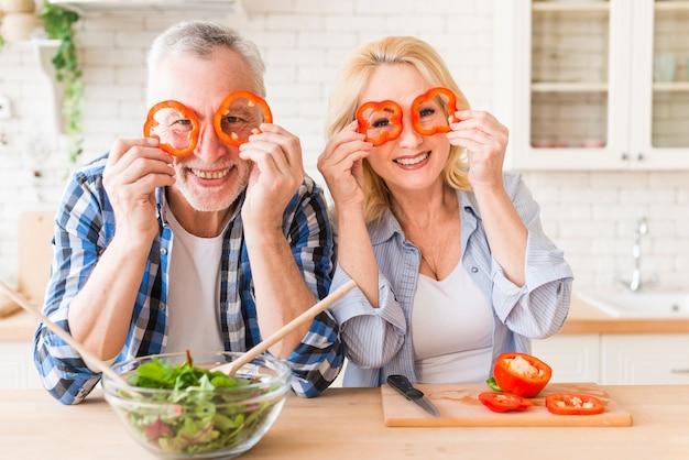 Retrato sonriente de un par mayor que mira a través de rebanada roja del paprika