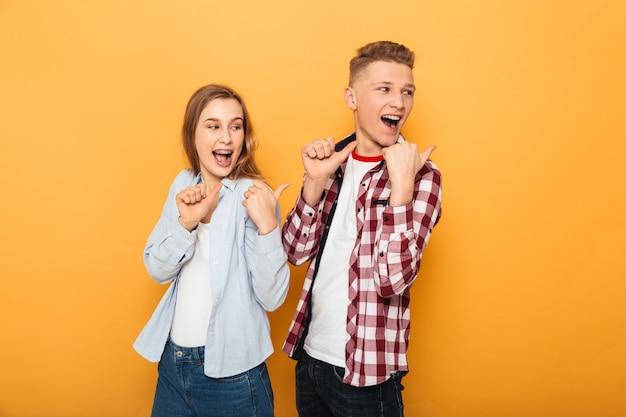 Retrato, de, un, sonriente, pareja adolescente, señalar con el dedo
