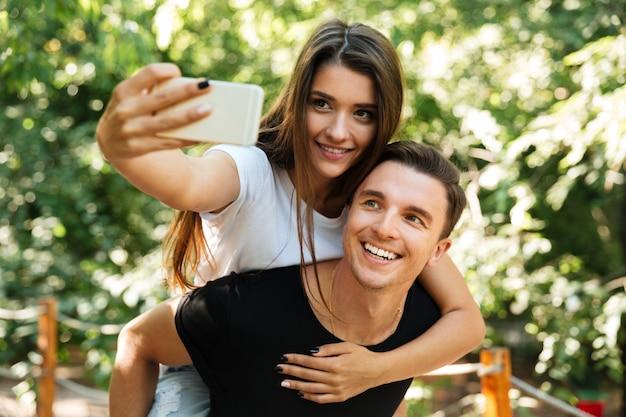 Retrato de una sonriente pareja atractiva en el amor haciendo selfie