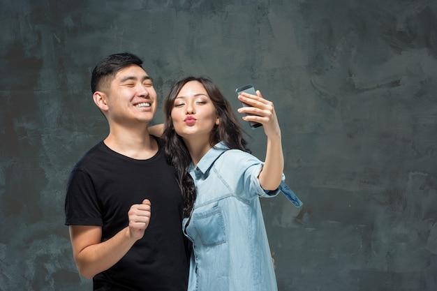 Retrato de la sonriente pareja coreana en un gris