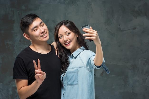 Retrato de sonriente pareja coreana haciendo foto selfie en un estudio gris