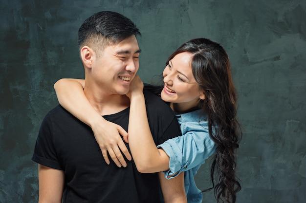 Retrato de la sonriente pareja coreana en una pared gris