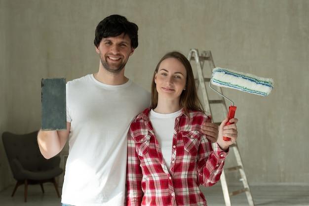 Retrato sonriente pareja de familia sosteniendo el rodillo y el cepillo de pintura pareja joven haciendo reparaciones en el hogar