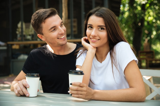 Retrato de una sonriente pareja feliz bebiendo café