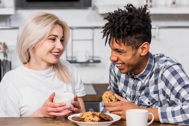 Retrato de sonriente pareja joven interracial desayunando juntos en casa