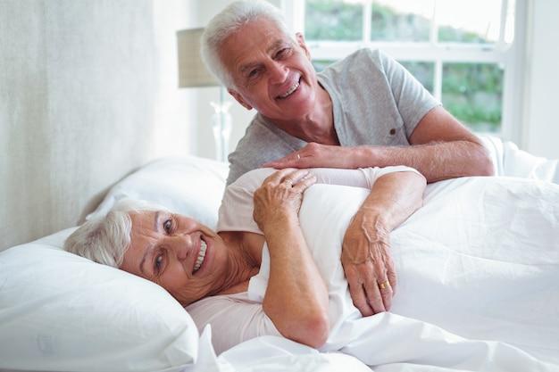 Retrato de sonriente pareja senior descansando en la cama