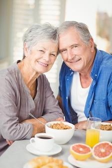 Retrato de la sonriente pareja senior en la mesa con desayuno