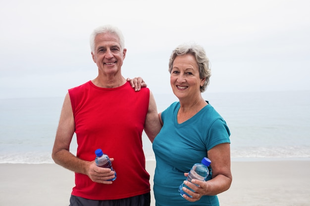 Retrato de sonriente pareja senior sosteniendo la botella
