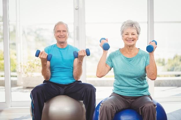 Retrato de la sonriente pareja senior sosteniendo pesas