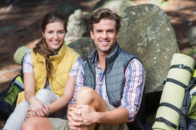Retrato de la sonriente pareja sentada en el campo