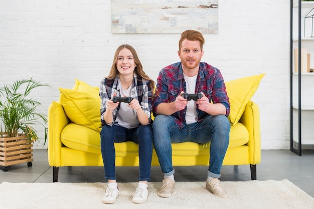 Retrato sonriente de los pares jovenes que se sientan en el sofá amarillo que juega a juegos con la consola del videojuego