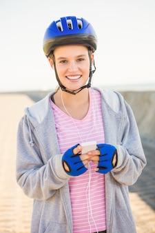 Retrato de sonriente patinador rubia deportivo disfrutando de la música en el paseo