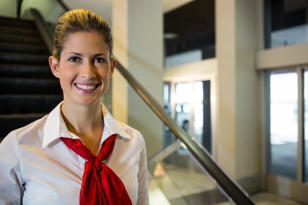 Retrato de sonriente personal femenino de pie en la escalera mecánica