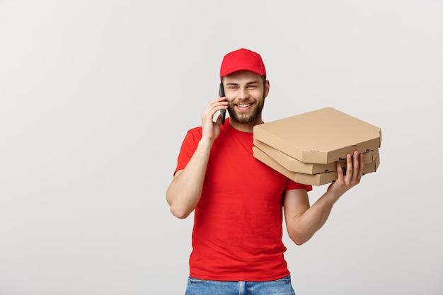 Retrato de un sonriente repartidor con gorra roja hablando por teléfono móvil mientras sostiene cajas de pizza