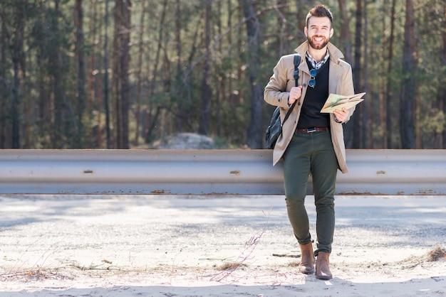 Retrato sonriente de un viajero masculino que sostiene su mochila y mapa