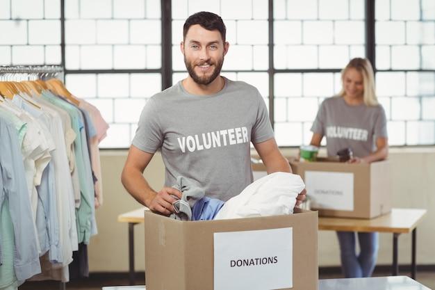 Retrato de sonriente voluntario separando ropa de caja de donación
