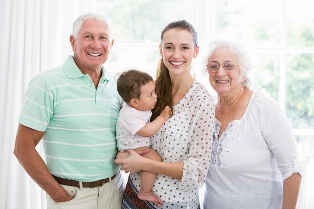 Retrato de sonrientes abuelos y madre con bebé