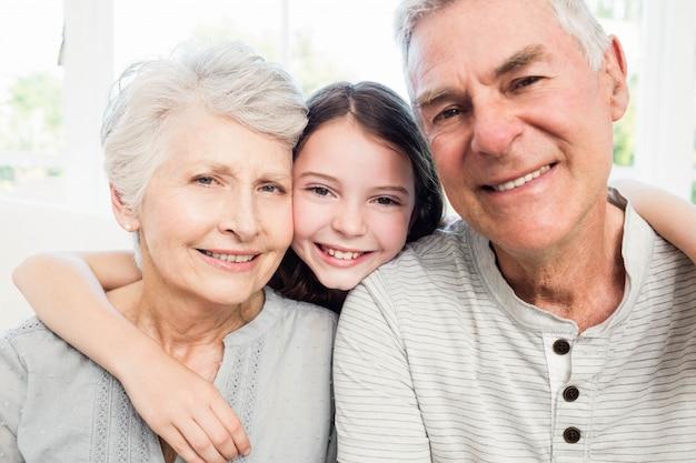 Retrato de sonrientes abuelos y nieta en el sofá